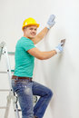 Smiling man in helmet doing renovations at home repair renovation and concept Royalty Free Stock Photography
