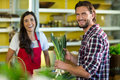 Smiling man holding a bunch of spring onions in the grocery store Royalty Free Stock Photo