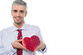 Smiling man holding a gift box senior heart shaped Royalty Free Stock Photography
