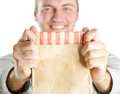 Smiling man holding out paper bag isolated white Royalty Free Stock Photo