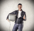Smiling man holding a vintage television young wearing cloths and an old Royalty Free Stock Photo