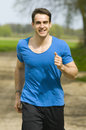 Smiling man jogging front frontal waist up a young in a blue t shirt when running training on a sand track with low depth of field Stock Photography
