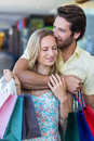 Smiling man kissing his girlfriend on forehead men at shopping mall Stock Photo