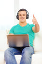 Smiling man with laptop and headphones at home technology music lifestyle concept showing thumbs up Royalty Free Stock Photos