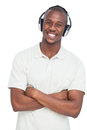 Smiling man listening to music with arms crossed on a white background Royalty Free Stock Image