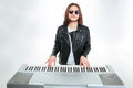 Smiling man with long hair in sunglasses playing on synthesizer Royalty Free Stock Photo
