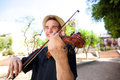 Smiling man outside playing violin Royalty Free Stock Photo