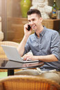 Smiling man on phone call at cafe with laptop Royalty Free Stock Photo