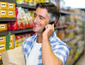 Smiling man on a phone call with grocery bag Royalty Free Stock Photo