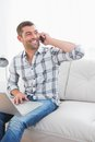 Smiling man on a phone with a laptop at home Royalty Free Stock Photo
