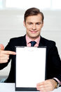 Smiling man pointing towards blank clipboard Royalty Free Stock Image