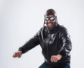 Smiling man posing as a motorcyclist funny young is wearing black leather jacket vintage cap and glasses isolated on white Royalty Free Stock Image