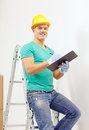 Smiling man in protective helmet with clipboard repair building and home concept Royalty Free Stock Photography