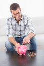Smiling man putting coins in a piggy bank Royalty Free Stock Photo