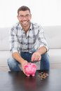 A smiling man putting coins in a piggy bank Royalty Free Stock Photo