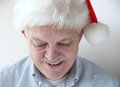 Smiling man in santa hat businessman wearing looks down and smiles Royalty Free Stock Photography