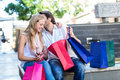 Smiling man with shopping bags kissing his girlfriend men while sitting on bench at mall Royalty Free Stock Photography