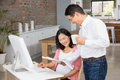 Smiling man showing newspaper to his pregnant wife men at home Stock Photography