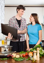 Smiling man shows the new recipe to girl men at kitchen table Stock Images