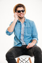Smiling man sitting on chair and talking by cell phone Royalty Free Stock Photo
