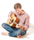 Smiling man sitting on floor and playing on acoustic guitar handsome Stock Images