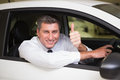 Smiling man sitting in his car giving thumbs up at new showroom Royalty Free Stock Image