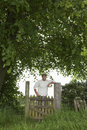 Smiling man standing across field gate portrait of a under the tree Royalty Free Stock Image