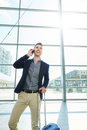 Smiling man standing in station with mobile phone and suitcase Royalty Free Stock Photo