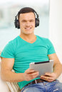 Smiling man with tablet pc and headphones at home technology music lifestyle concept Royalty Free Stock Photo