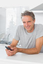 Smiling man texting in kitchen looking at camera Stock Photography