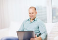 Smiling man working with laptop at home technology business and lifestyle concept Stock Images