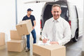 Smiling manager standing behind stack of cardboard boxes