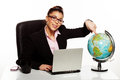 Smiling manageress pointing to a globe or businesswoman wearing glasses sitting at her desk north america on world Royalty Free Stock Image