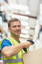 Smiling manual worker scanning package Royalty Free Stock Photo
