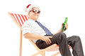 Smiling mature businessman with santa hat sitting on a chair and beach drinking beer isolated white background Royalty Free Stock Photo