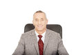 Smiling mature businessman sitting on armchair Royalty Free Stock Photo