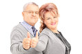 Smiling mature couple giving thumbs up and looking at camera isolated on white background Royalty Free Stock Images