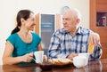 Smiling mature couple having tea at home interior Stock Photo