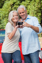 Smiling mature couple looking at pictures on their camera while leaning against cabriolet Stock Photography