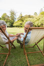 Smiling mature couple lying on sun loungers and looking at camera Stock Image