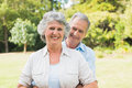 Smiling mature couple in the park embracing and looking at camera Royalty Free Stock Image