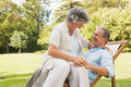 Smiling mature couple in park smilig on sun lounger Stock Photography