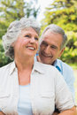 Smiling mature couple in park together embracing and laughing Stock Photography