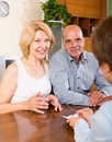 Smiling mature couple of pensioners talking with employee at office Royalty Free Stock Photos