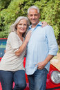 Smiling mature couple posing against their red cabriolet Royalty Free Stock Image