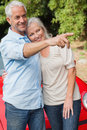 Smiling mature couple posing by their red convertible on bright day Royalty Free Stock Photography