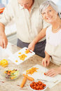 Smiling mature couple preparing food Royalty Free Stock Photos