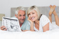 Smiling mature couple reading newspaper in bed portrait of a at home Royalty Free Stock Photo