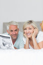 Smiling mature couple reading newspaper in bed portrait of a at home Stock Photo