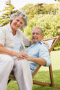 Smiling mature couple resting on sun lounger and looking at camera Royalty Free Stock Photo